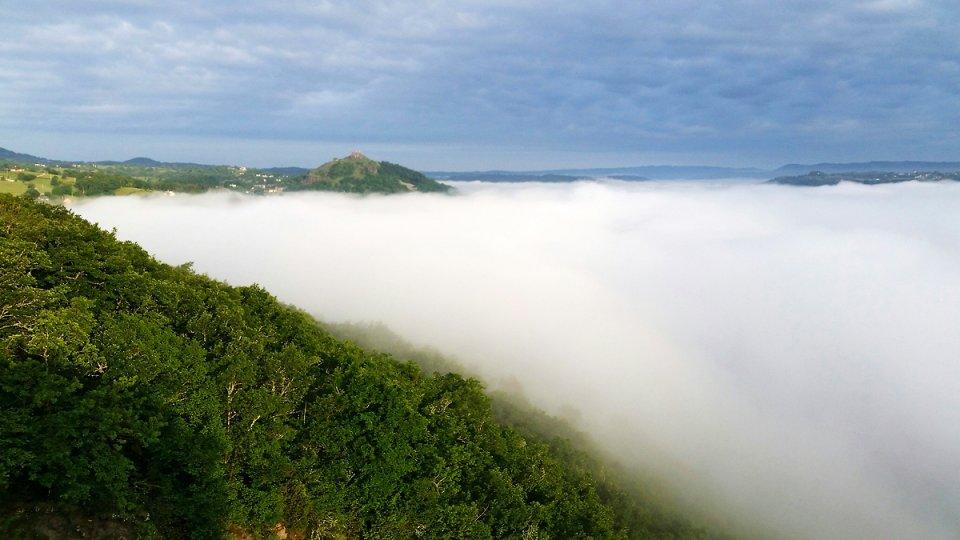 Le château de Calmont d'Olt émerge du brouillard matinal